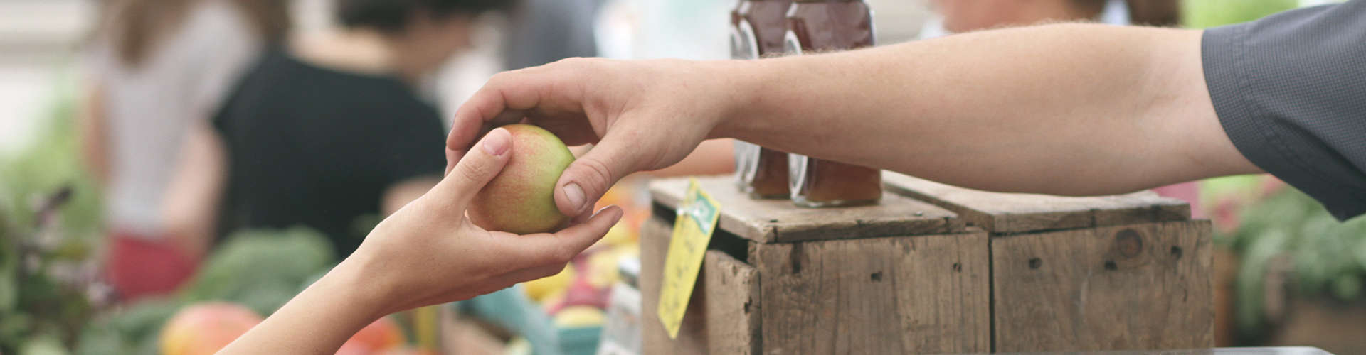 רוכל מעביר פרי ללקוח בסיור בשוק