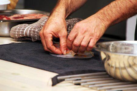 ידיים מגלגלות ספרינג רול עם מגבת וקעריות בצד