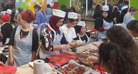 מורות ותלמידות מבשלות בפעילות לבית הספר שלהן